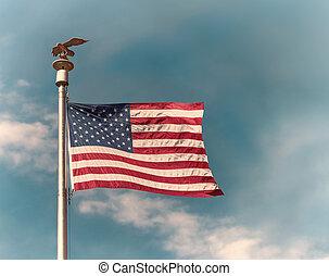 bandera estadounidense, en, poste, ondulación, en el viento, contra, cielo azul, plano de fondo