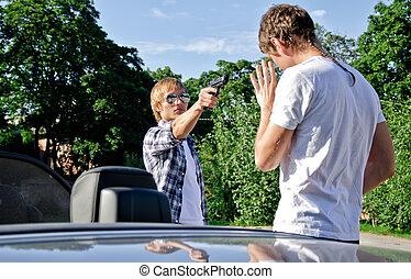 Bandit with a gun threatening young man near the car