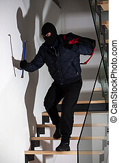 Bandit with crowbar on stairs