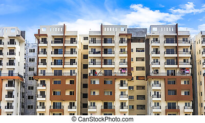 Bangalore, Karnataka, India - December,12, 2015: A high rise modern apartment complex in suburban Bangalore against a blue sky on a sunny day.