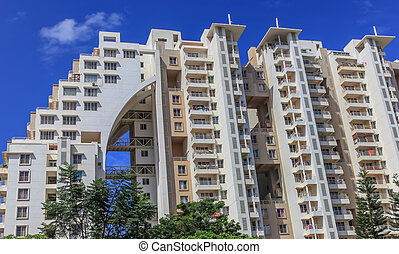 A high rise modern apartment complex in suburban Bangalore against a blue sky on a sunny day.