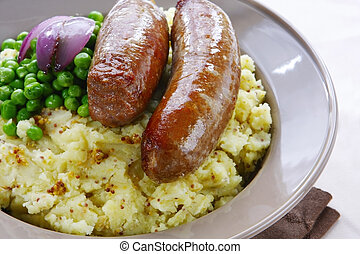 Bangers and mash ~ sausages over mashed potato with seeded mustard, green peas, and grilled red onion.