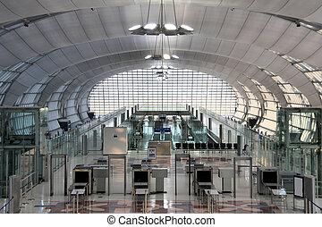 Modern interior of famous Bangkok Suvarnabhumi International Airport. Security control machines and departures area.