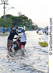 Bangkok-Nov 08 : people push motorcycle on water flood road,...