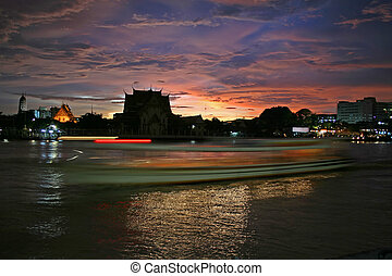 Bangkok River at Sunset - A boat leaves streaking lights on...