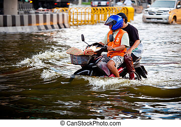 Two men on a motorbike navigating through the flood