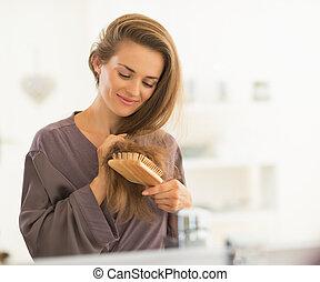banheiro, mulher, jovem, cabelo, combing, feliz