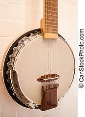 Banjo hanging on white brick wall