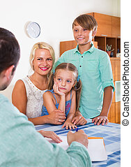 Bank agent consulting family with kids in home interior