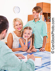 Bank agent consulting family with kids in the home interior