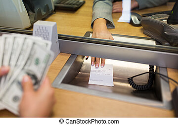 bank clerk giving receipt to customer with money - people,...