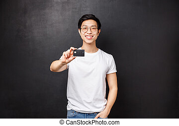 Bank, finance and payment concept. Portrait of friendly confident young asian male showing credit card at camera with pleased beaming smile, advice open account at put money, black background