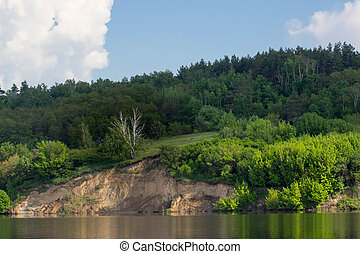 bank of river with green trees on summer day. Blue sky with...