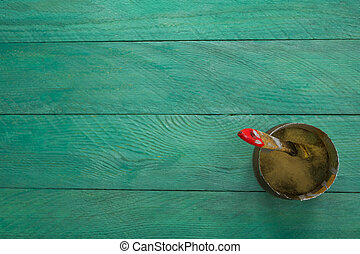 Bank paints and brush on a turquoise wooden background -...