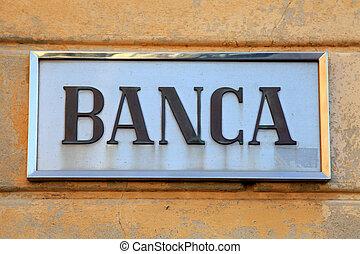 Bank sign on stone wall facade, Italy