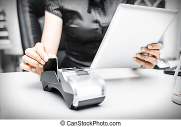 Bank terminal and tablet pc - Female hand holding bank...