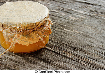 bank with honey on a gray wooden background . Side view