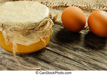 bank with honey with raw eggs. on a gray wooden background . Side view. Agriculture.