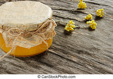 bank with honey with yellow dry flowers on a gray wooden background . Side view