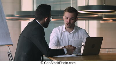 Confident caucasian male financial advisor bank worker broker explaining deal benefits, showing presentation on computer to focused arabic businessman, shaking hands after making agreement in office.