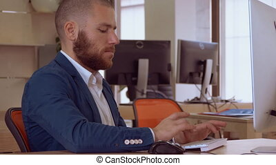 bank worker using pc - handsome caucasian man with beard...