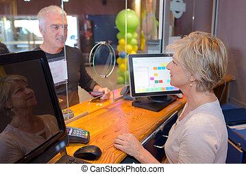 banker at her desk counter attending a customer