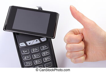 Hand of woman showing thumbs up and payment terminal with mobile phone with NFC technology