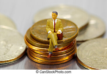 Banking - Miniature Businessman Sitting on Pennies