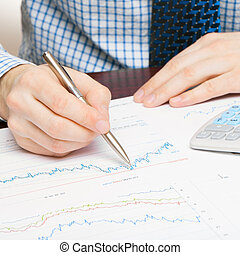 Banking, taxing and all things related with world of finance - close up studio shot of a man working with some financial data