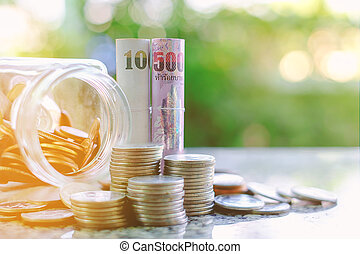 Banknote and coins in and outside the glass jar, Thai Baht...