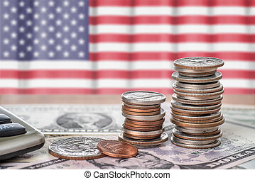 Banknotes and coins in front of the national flag of the USA