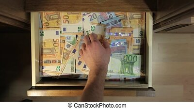 Grabbing cash money banknotes from a drawer in a pile