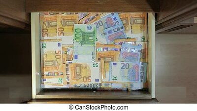 Puttin cash money banknotes in a drawer in a pile