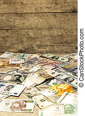 banknotes by all countries in front of wooden background