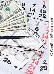 Banknotes of dollars on calendar sheets closeup