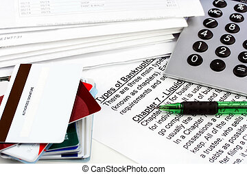 Bankruptcy document with bills, credit cards, calculator and pen. Copy space on one blank credit card.