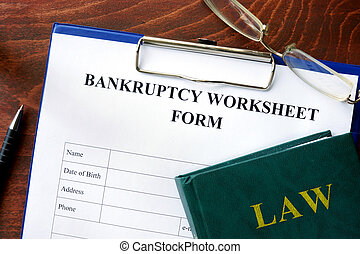Bankruptcy worksheet form on a wooden table.