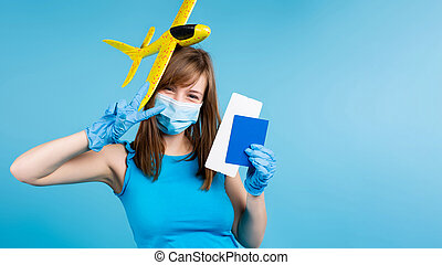 Banner. A blonde girl in a medical mask and protective gloves, illuminating toy plane on head, a passport and air tickets. Dreaming of traveling on a blue background with blank advertising space.