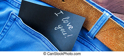 banner for website, the phrase, a note I love you in the jeans pocket, on a wooden background, space for text