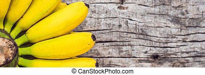 BANNER, Long Format Bunch of raw ripe organic yellow bananas on wooden background
