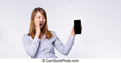 Banner- long format. Excited woman screaming, hold mobile phone with blank black empty screen, isolated on gray background. People sincere emotions, lifestyle, advertisement . Mock up copy space.