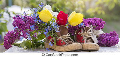 Banner of a bouquet of summer flowers in old shoes.