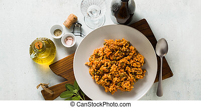 banner of Italian risotto with tomato sauce and green peas, served in a plate on a wooden cutting board and a bottle of red sparkling wine . classic Mediterranean cuisine. healthy vegan meal for the whole family