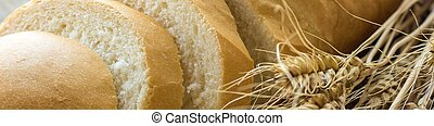 Banner of Sliced bread with wheat spikes on wooden table closeup