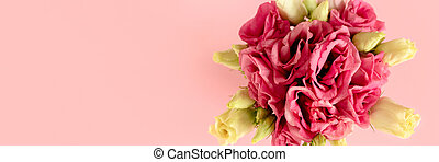 Banner with bouquet of eustoma flowers on pink pastel background.