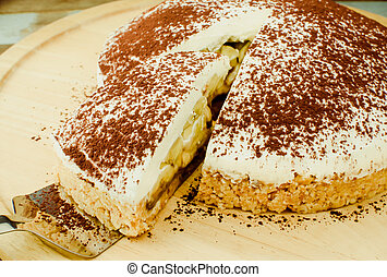 Banoffee pie on wooden plate in sof