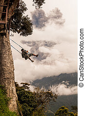 Banos De Agua Santa, - 08 March 2016: Happy Adult Caucasian Man Swinging On A Swing In Banos De Agua Santa, Tungurahua Volcano Explosion On March 2016 In The Background, Ecuador, South America In Banos De Agua Santa On March 08, 2016