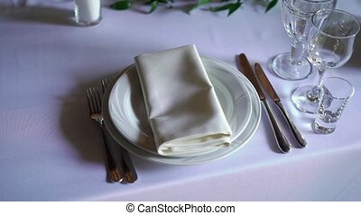 Banquet decorated table, with cutlery. Wedding decor in the banquet hall. Serving of a festive table, plate, napkin, knife, fork. Table setting decoration. Romantic Dinner or other events.