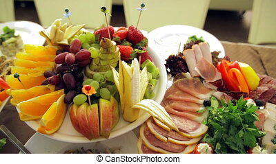 Banquet: dishes with fruit, fish and meat are on the table