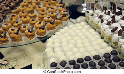 Banquet table and laid out a variety of small cakes, candies, white and dark chocolate and a glass of with dessert.